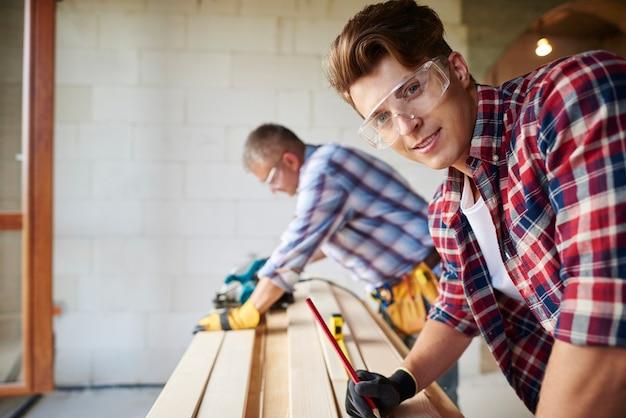 経験豊富な大工と彼の若い従業員のクローズアップ
