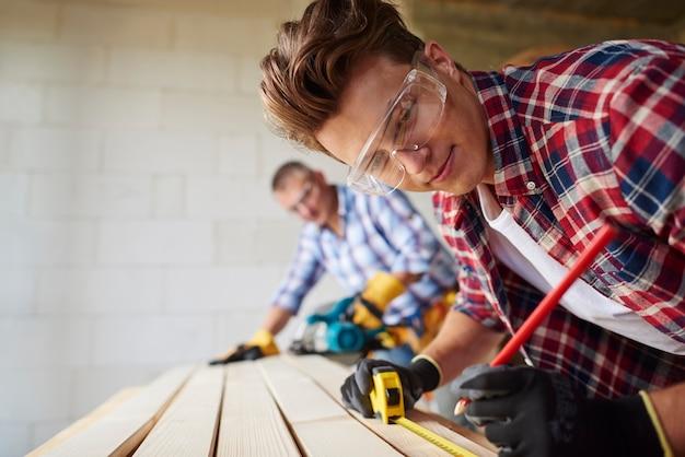Крупным планом опытный плотник и его младший сотрудник