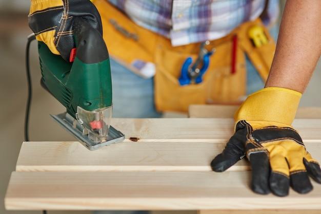 木の板での経験豊富な大工の穴あけのクローズアップ