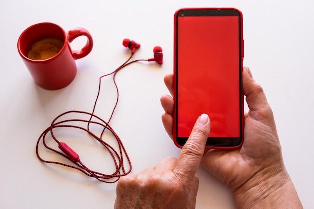 빨간 화면이 있는 전화를 사용하여 여성의 손을 클로즈업합니다. 커피 컵과 이어폰이 있는 흰색 데스크탑