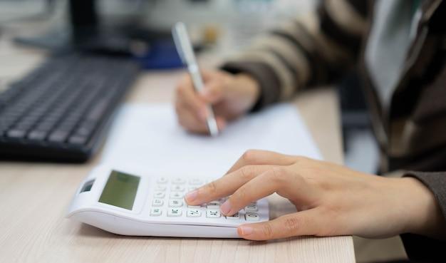 働く女性の概念のための計算のための計算機の指の手押しでクローズアップ