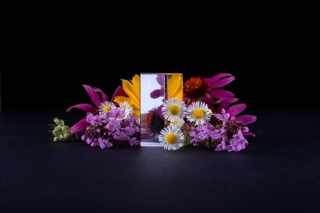 製品のプレゼンテーションのための花とガラスの表彰台にクローズアップ