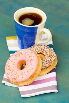 コーヒーカップの横にある新鮮なドーナツをクローズアップ