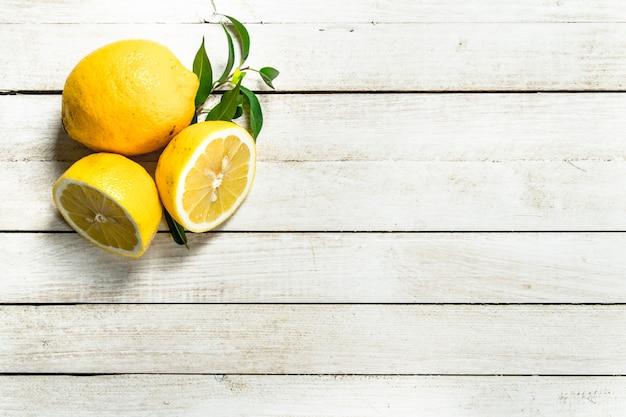 Крупным планом на свежие спелые лимоны с листьями