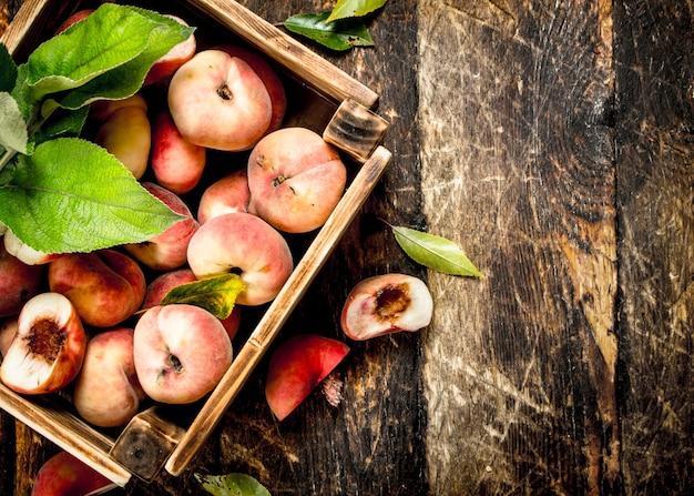 Крупным планом свежие спелые персики в коробке