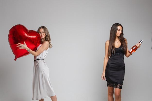 Крупным планом друзей в серебряных и черных платьях позируют