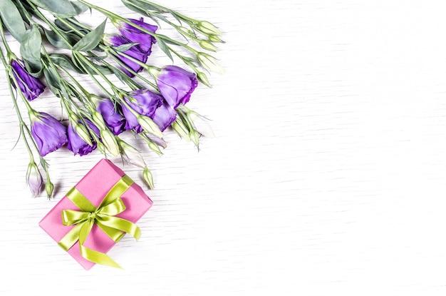 Закройте вверх на подарочной коробке и изолированных цветках