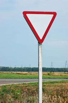 Крупным планом на дорожный знак уступить дорогу и голубое небо.
