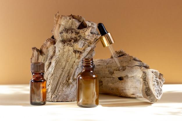 Крупным планом на стеклянной косметической бутылке с пипеткой рядом с деревянным бруском