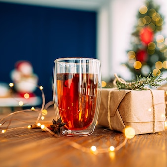 ガーランドライトが付いている木製のお祝いのテーブルの上のスターアニスと紅茶のガラスのマグカップにクローズアップ
