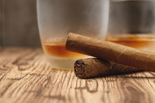 Крупным планом на стакан виски и скрученные сигары