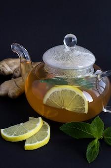 Крупный план на стеклянном чайнике с лимоном, имбирем и медом на черном фоне. расположение вертикальное.