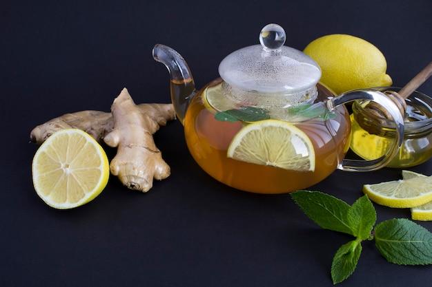 Крупный план на стеклянном чайнике с лимоном, имбирем и медом на черном фоне