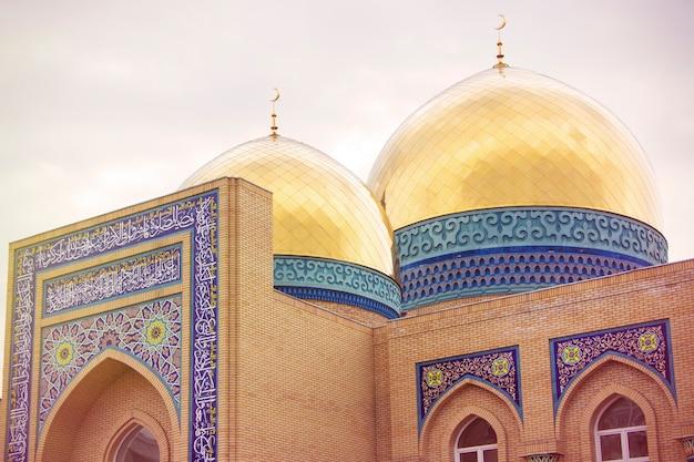Закройте на золотой купольной мечети