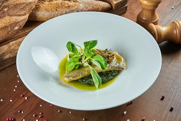 グリーンソース添え煮ほうれん草の枕の上パイクパーチのグルメグリルフィレをクローズアップ。健康食品。レストランの料理。