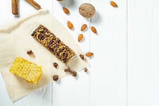 Закройте вверх на баре granola с сотами, гайками и циннамоном на бумаге ремесла на белой деревянной предпосылке.