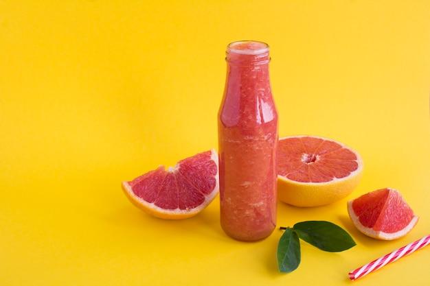 黄色の背景のガラス瓶にグレープフルーツのスムージーのクローズアップ。スペースをコピーします。
