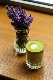 나무 테이블에 유리에 녹색 말차 음료에 닫습니다