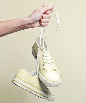 靴ひもでスニーカーを持っている手でクローズアップ