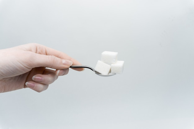 Закройте вверх по руке, держа ложку с кубиками белого сахара