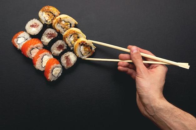 Крупным планом на руке, держащей суши-ролл с палочками для еды