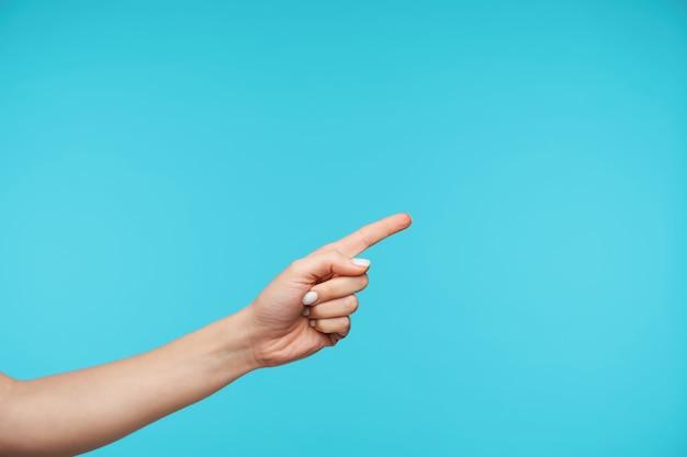 Крупным планом под рукой, держа указательный палец поднятым, показывая пустое пространство