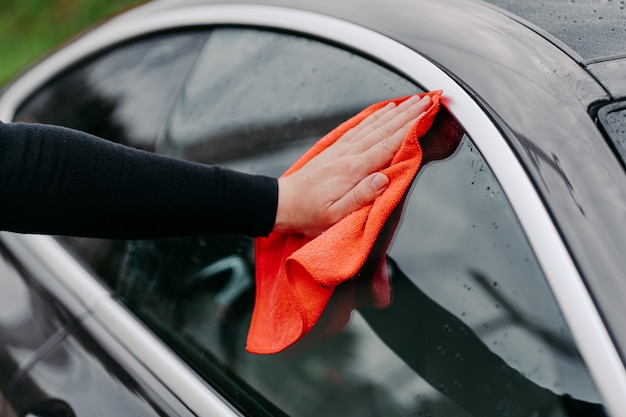 Крупным планом под рукой с тряпкой для чистки бокового окна черного автомобиля