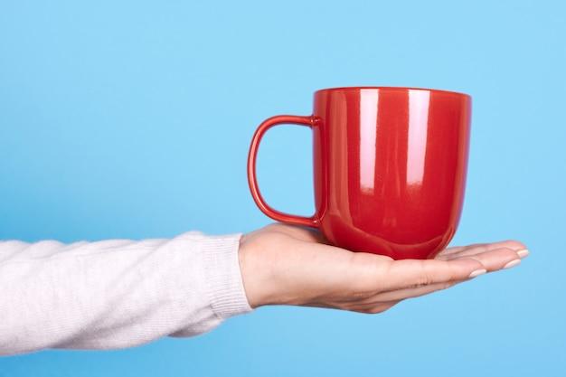 手に赤いマグカップとハンドルをクローズアップ