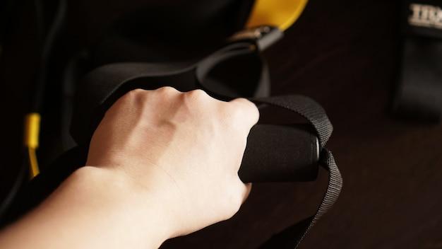 サスペンショントレーニングをしている手のクローズアップ-自宅でのスポーツ