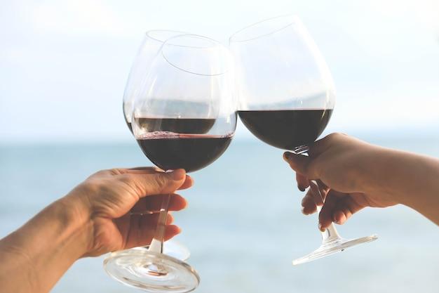 ビーチで赤ワイングラスを持って手をクローズアップ、お祝いのコンセプト