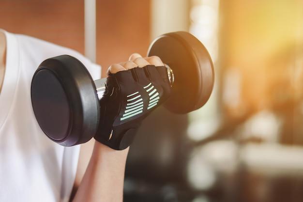 Крупным планом на руках, поднимающих гантели в фитнес-зале