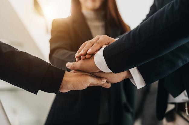 Крупным планом на руках деловых людей соединяют руки вместе над концепцией единства в лучах солнца