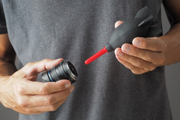 손에 클로즈업은 송풍기를 사용하여 카메라 렌즈를 부드럽게 청소합니다.