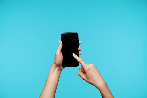 Крупным планом на руках с белым маникюром, держа смартфон и проводя по экрану