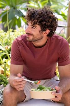Крупным планом на красивый мужчина ест в парке