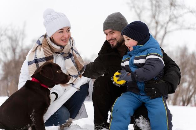 犬と雪の中で遊んで幸せな家族にクローズアップ