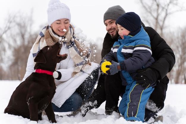 Крупным планом счастливая семья, играющая в снегу с собакой