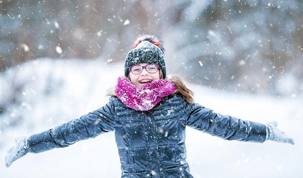 冷ややかな冬の公園で幸せな女の子にクローズアップ