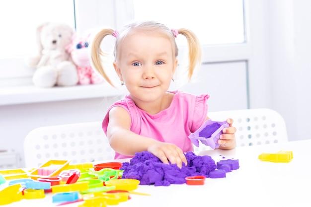 Крупным планом счастливая девушка играет с красочным кинетическим песком
