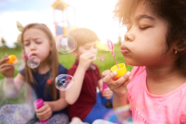 シャボン玉で遊んで幸せな子供たちにクローズアップ