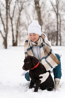 Крупным планом счастливая мать играет в снегу с собакой