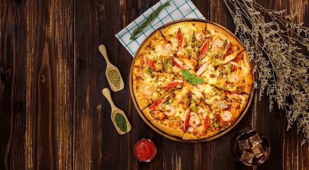 エビ、ピーマン、カニカマと冷たい飲み物、ナプキン、トマトソースまたはケチャップの材料、乾燥植物、パプリカチリパウダー、オレガノを添えた自家製シーフードピザをクローズアップします。