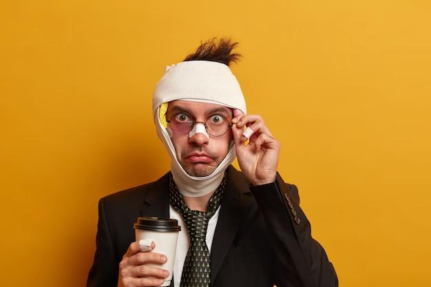 Крупным планом - раненый мужчина с темным синяком под глазами и сотрясением мозга, носит повязку