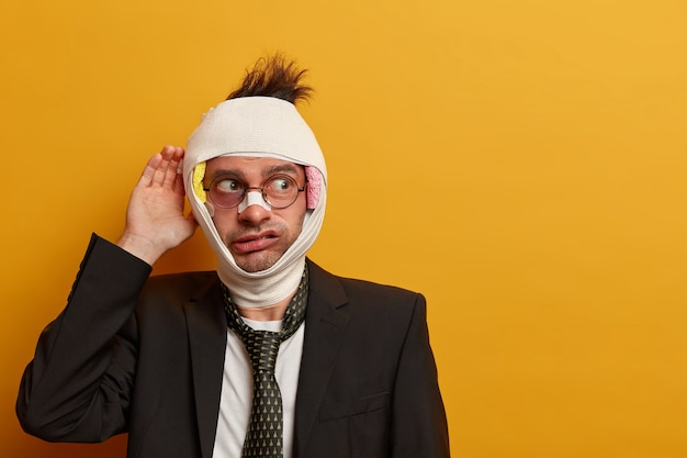 目の下の暗い打撲傷と脳震盪で負傷した男性にクローズアップ、包帯を着用
