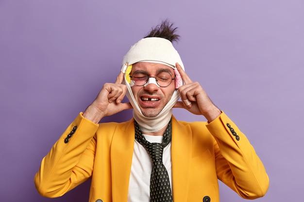 눈과 뇌진탕 아래에 어두운 타박상이있는 부상당한 남자를 닫고 붕대를 감습니다.
