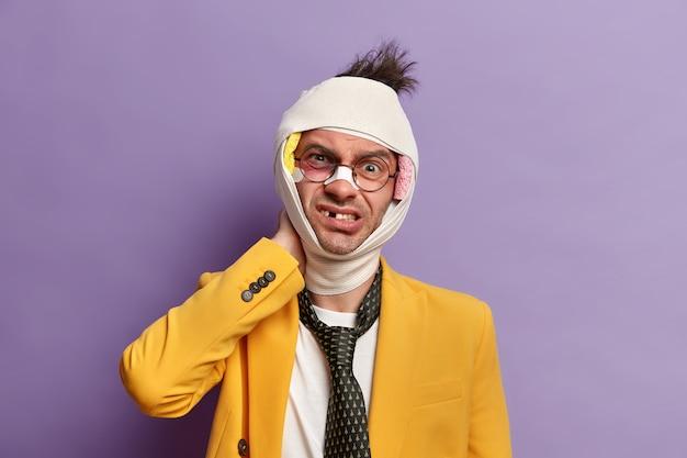 눈과 뇌진탕 아래에 어두운 타박상이있는 부상당한 남자를 닫고 붕대를 감습니다. 무료 사진