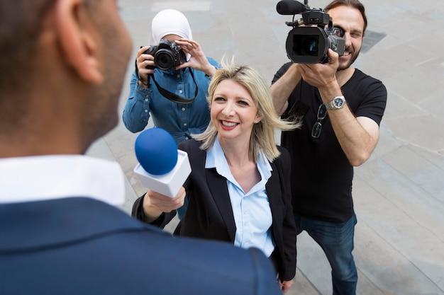 Крупный план интервьюируемого с микрофоном, принимающим заявления