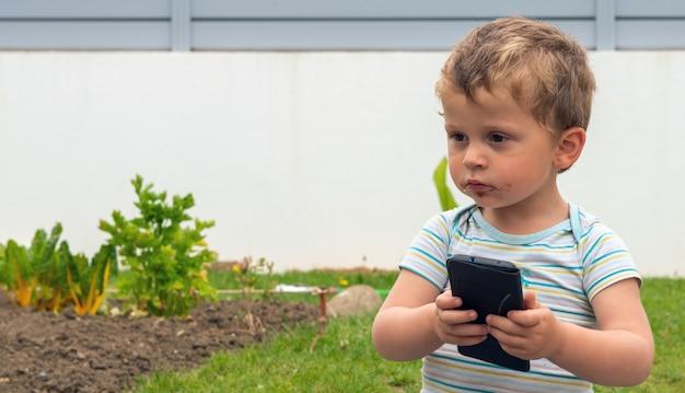 公園で携帯電話を使用して子供にクローズアップ