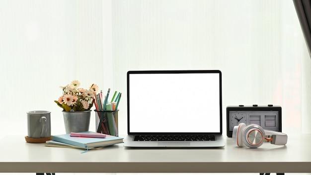 Крупным планом на ноутбук, головной телефон, ноутбук и чашку кофе на белом столе