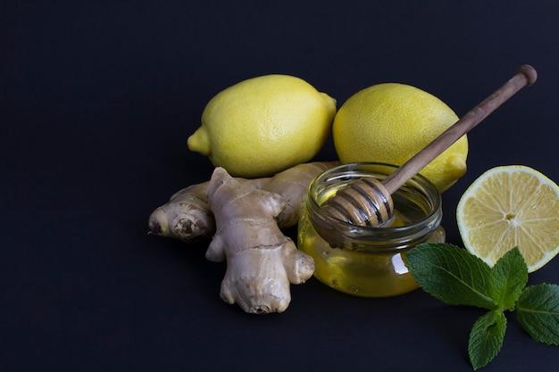 黒の背景にレモン、生姜、蜂蜜のクローズアップ。お茶の材料。スペースをコピーします。